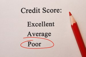 "Image of paper and red pencil with the words ""Credit Score"" at the top and ""Poor"" circled in red below it."
