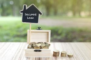 """Image of a wooden box filled with coins and a house shaped sign that reads """"Secured Loan""""."""