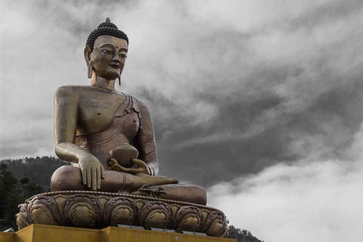 gold buddha statue under cloudy sky