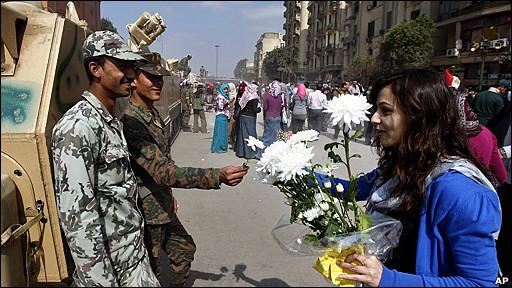 Una mujer da flores a los militares.