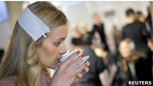 Modelo bebe xícara de café durante a Milan Fashion Week, em 22 de setembro de 2011