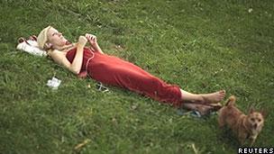 Mulher usa tocador de MP3 em parque (Reuters)