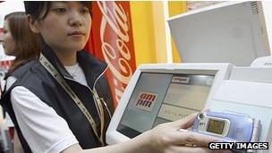 Un consumidor pega su celular a un lector  inalámbrico