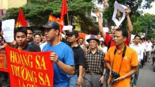 Blogger Người Buôn Gió (áo da cam, bìa phải) trong một cuộc biểu tình chống Trung Quốc