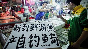 Người bán cá ở một khu chợ ở Bắc Kinh