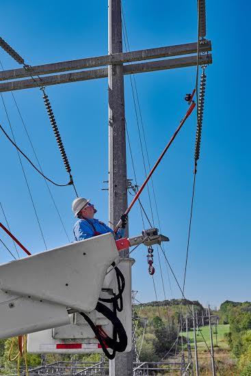 Lineman, Ritney Smith (291638), working on transmission lines near Greenville, South Carolina. SC; lineman; line crew; line work; transmission towers; bucket trucks; hot stick; insulators