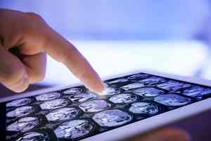 Radiologist hand touching modern digital tablet, close up
