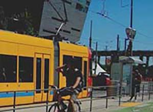 bicyclist and light rail train and station