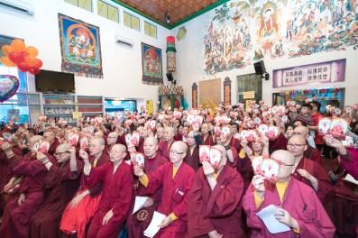 圖為佛子高舉「聳立50 傳承永續」的師尊相片。