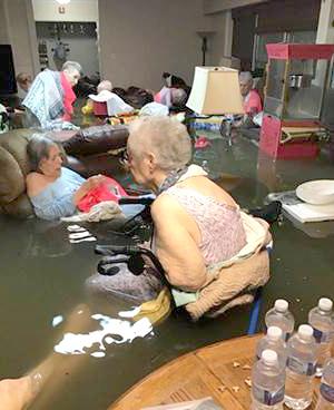 一間養老院被積水給淹沒,坐著輪椅和行動不便的老人泡在水中等待救援