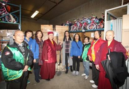 上師與法師、義工在大溫聖誕局倉庫留影。身後為捐贈的一箱一箱的衣物。