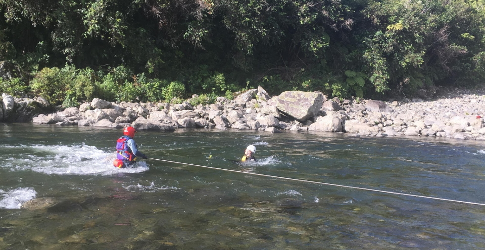 A person floats down the river about to hit the strainer