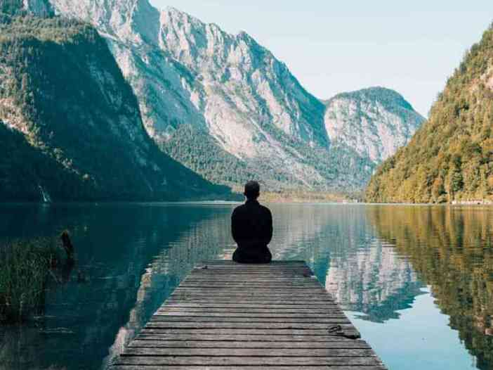 Lonely boy sitting behind the lake image