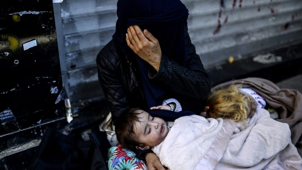A Syrian Kurdish refugee woman with her daughter waits for help, abandoned and alone