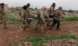 Syrian Army fighters carry a wounded colleague in Afrin, Syria.
