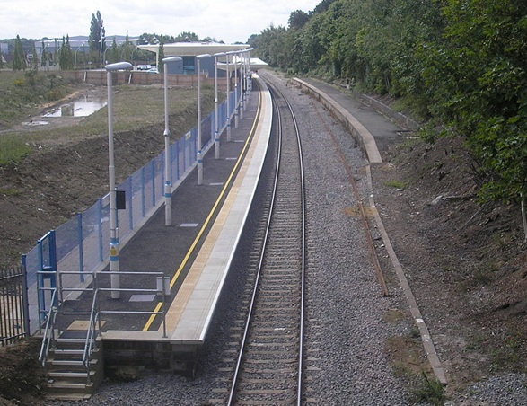 Image of Corby station showing new platform on the left, slightly curving to the left as it recedes into the distance. On the right is the old shorter platform. There is currently no passenger access to the second platform.