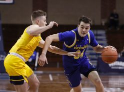 SIOUX FALLS, SD - NOVEMBER 25: Alex Arians #34 of the South Dakota State Jackrabbits drives past Sean McNeil #22 of the West Virginia Mountaineers during the Bad Boy Mowers Crossover Classic at the Sanford Pentagon in Sioux Falls, SD. (Photo by Richard Carlson/Inertia)