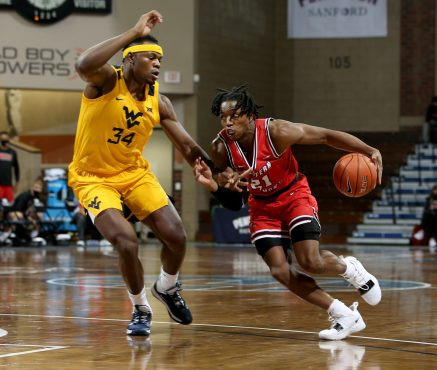 SIOUX FALLS, SD - NOVEMBER 27: Kenny Cooper #21 of the Western Kentucky Hilltoppers drives to the basket against Oscar Tshiebwe #34 of the West Virginia Mountaineers during the Bad Boy Mowers Crossover Classic at the Sanford Pentagon in Sioux Falls, SD. (Photo by Dave Eggen/Inertia)