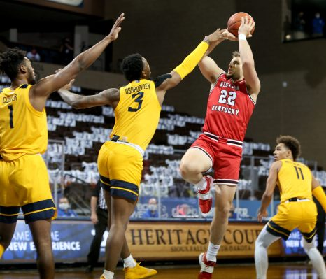 SIOUX FALLS, SD - NOVEMBER 27: Carson Williams #22 of the Western Kentucky Hilltoppers shoots over Gabe Osabuohien #3 of the West Virginia Mountaineers during the Bad Boy Mowers Crossover Classic at the Sanford Pentagon in Sioux Falls, SD. (Photo by Dave Eggen/Inertia)