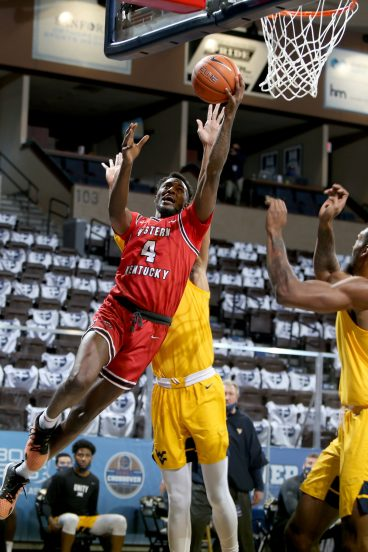 SIOUX FALLS, SD - NOVEMBER 27: Josh Anderson #4 of the Western Kentucky Hilltoppers takes the ball to the basket against the defense from the West Virginia Mountaineers during the Bad Boy Mowers Crossover Classic at the Sanford Pentagon in Sioux Falls, SD. (Photo by Dave Eggen/Inertia)