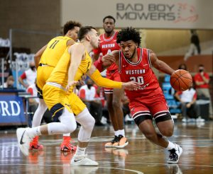 SIOUX FALLS, SD - NOVEMBER 27: Dayvion Mcknight #20 of the Western Kentucky Hilltoppers dives against Jordan McCabe #5 of the West Virginia Mountaineers during the Bad Boy Mowers Crossover Classic at the Sanford Pentagon in Sioux Falls, SD. (Photo by Dave Eggen/Inertia)