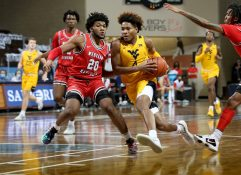 SIOUX FALLS, SD - NOVEMBER 27: Miles McBride #4 of the West Virginia Mountaineers drives against Dayvion Mcknight #20 of the Western Kentucky Hilltoppers during the Bad Boy Mowers Crossover Classic at the Sanford Pentagon in Sioux Falls, SD. (Photo by Dave Eggen/Inertia)