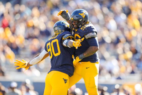 Oct 17, 2020; Morgantown, West Virginia, USA; West Virginia Mountaineers defensive lineman Akheem Mesidor (90) celebrates with defensive lineman Darius Stills (56) after a defensive stop during the third quarter against the Kansas Jayhawks at Mountaineer Field at Milan Puskar Stadium. Mandatory Credit: Ben Queen-USA TODAY Sports