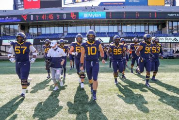 Oct 3, 2020; Morgantown, West Virginia, USA; West Virginia Mountaineers linebacker Dylan Tonkery (10) leads his team onto the field prior to their game against the Baylor Bears at Mountaineer Field at Milan Puskar Stadium. Mandatory Credit: Ben Queen-USA TODAY Sports