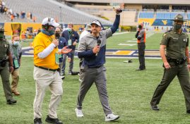 Oct 3, 2020; Morgantown, West Virginia, USA; West Virginia Mountaineers head coach Neal Brown celebrates with fans after his team defeated the Baylor Bears at Mountaineer Field at Milan Puskar Stadium. Mandatory Credit: Ben Queen-USA TODAY Sports