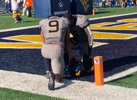 Isaiah Esdale, 9, and Leddie Brown, 4, pray prior to Saturday's kick off in the end zone.