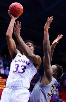 Kansas forward David McCormack (33) turns for a shot over West Virginia forward Oscar Tshiebwe (34) during the first half, Tuesday, Dec. 22, 2020 at Allen Fieldhouse.