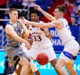 West Virginia guard Sean McNeil (22) gets a ball past Kansas forward David McCormack (33) and Kansas guard Christian Braun (2) during the first half, Tuesday, Dec. 22, 2020 at Allen Fieldhouse.