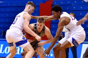 KU's Christian Braun, left, and David McCormack trap West Virginia's Sean McNeil during the first half of Tuesday night's Big 12 Conference game at Allen Fieldhouse.