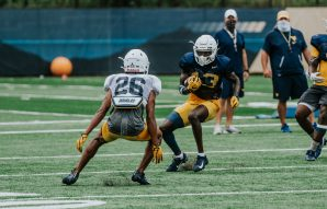 Cornerback Daryl Porter (26) looks to tackle receiver Sam James (13). WVU Athletics