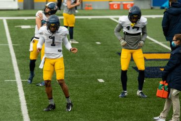 A pair of WVU players dance in between drills during a practice in Milan Puskar Stadium on Saturday April 17, 2021. Duncan Slade/WVSN
