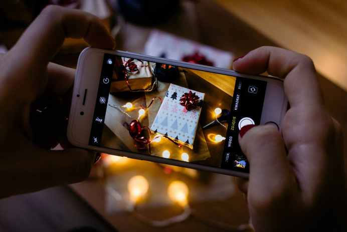 person using iphone taking picture of gift box boîte cadeau techno