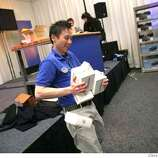 Phil Leung, Best Buy wireless expert, struggles with an armful of merchandise while stocking the shelves at the Best Buy store at Macworld Conference & Expo which opened on Monday January 14, 2008 in San Francisco, CA. The Expo starts on Tuesday.  Lea Suzuki/ The Chronicle