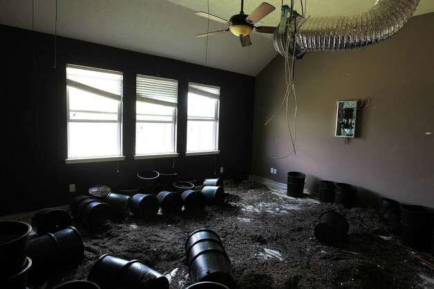 Plastic pots and potting soil cover the home's floor, and a makeshift electrical panel is mounted on the wall. The panel was used to power the lights to encourage growth and air ducts that sucked odors into the attic. Photo: James Nielsen / © Houston Chronicle 2012