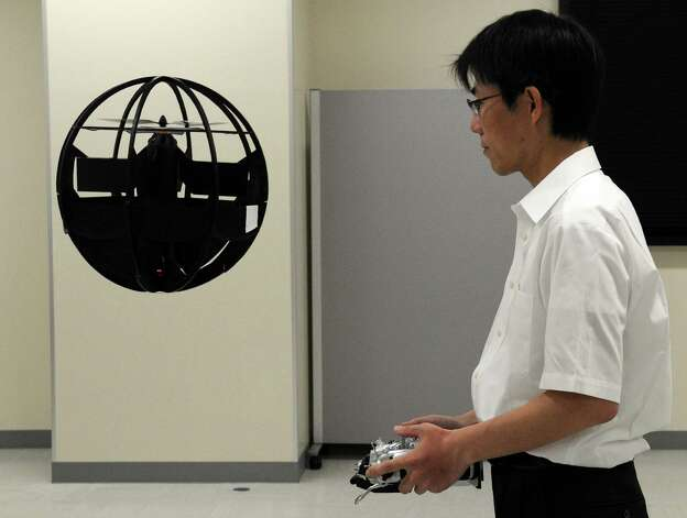 Japan Advanced Defense Technology Centre Engineer Fumiyuki Sato displays his spherical observation drone in Tokyo on July 22, 2011. The drone can fly down narrow alleys, hover on the spot, take off vertically and bounce along the ground. Photo: TOSHIFUMI KITAMURA, AFP/Getty Images / 2011 AFP
