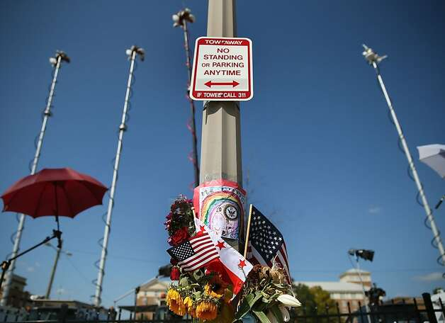 WASHINGTON, DC - SEPTEMBER 19: Condolence notes and flowers are hung on a pole across the street from the front gate of the Washington Navy Yard, September 19, 2013 in Washington, DC. On September 16 Aaron Alexis entered a building at the Washington Navy Yard and shot and killed 12 people before being shot and killed by police.  (Photo by Mark Wilson/Getty Images) Photo: Mark Wilson, Getty Images