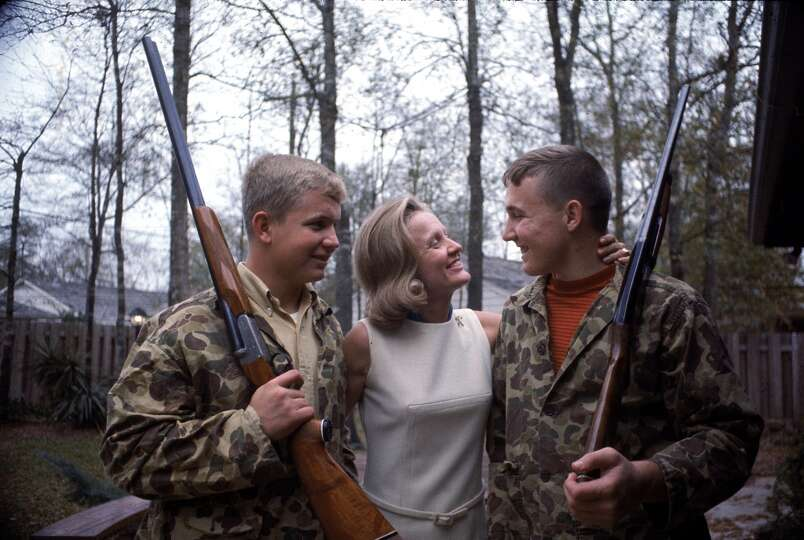 Sue Borman hugs her sons Fred and Ed, both of whom wear camouflage jackets and hold shotguns, Housto