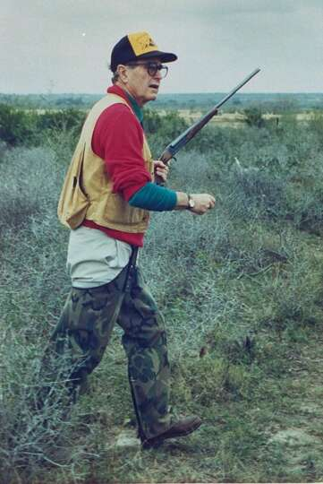 US Pres. George Bush aptly dressed in hunting gear w. rifle in hand hunting quail on the Lazy F ranc