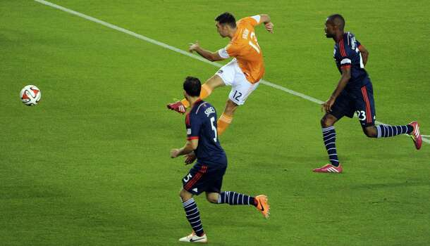 Houston's Will Bruin scores a goal in the second minute past New England's A.J. Soares, left, and Jose Gonclaves during the first half of a MLS soccer game, Saturday, March 8, 2014, at BBVA Compass Stadium in Houston. Photo: Eric Christian Smith, For The Chronicle