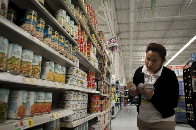 Walmart employee Laxmi Shasithakuri organizes cans of organic products on shelves at the store in Oakland. Photo: Sam Wolson, Special To The Chronicle