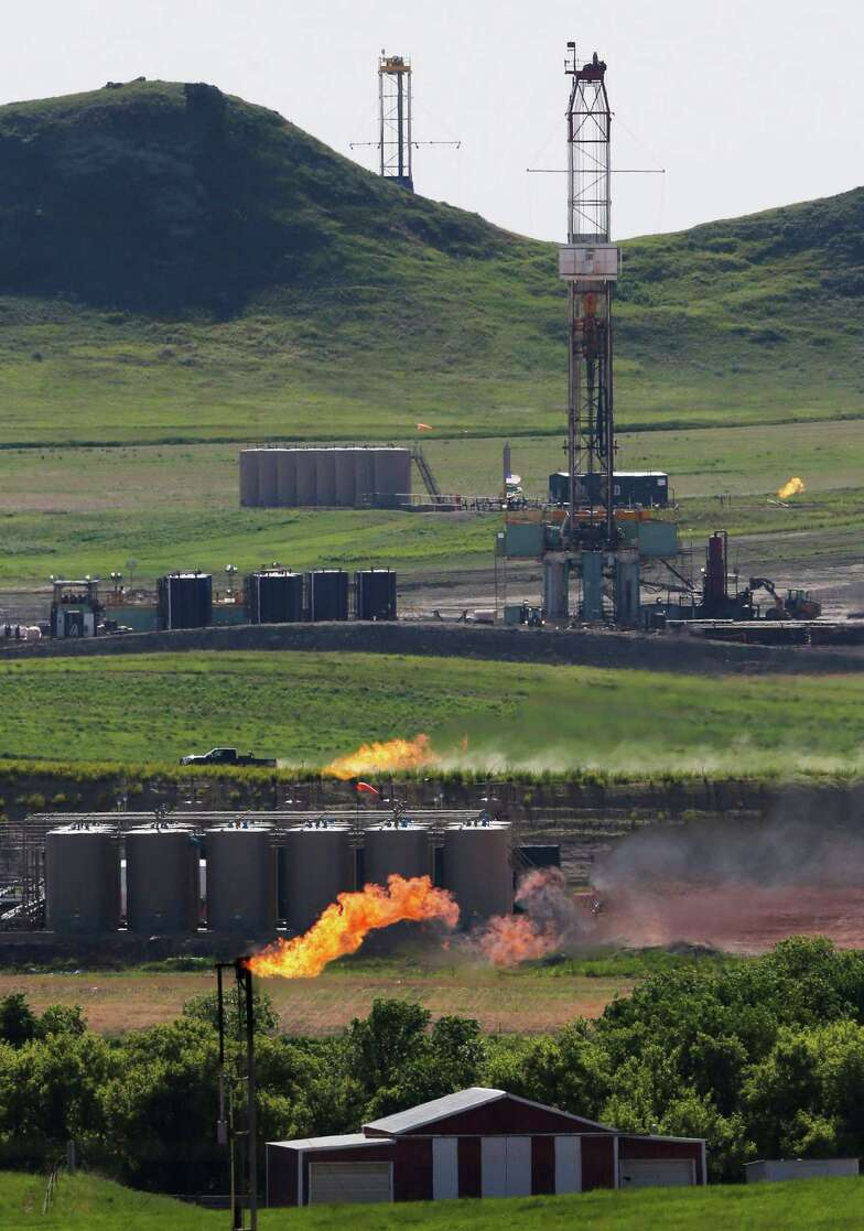 Flares like this one at an oil production facility in North Dakota burn off methane that is produced along with oil but is too costly to process and transport.(AP Photo/Charles Rex Arbogast, File)