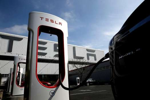 Tesla electric cars and charging stations are lined up outside the customer delivery center in front of Tesla Motors, California's only full-scale auto manufacturing plant. Photo: Michael Macor, The Chronicle
