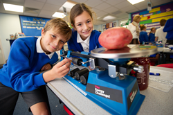 Children smiling near triple beam balance