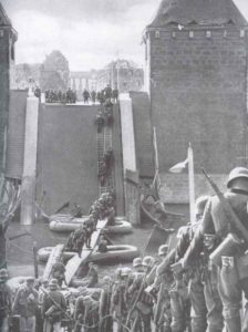 German infantry is crossing a blown up bridge over river Meuse