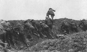 An officer is leading a section of British infantry out of a trench