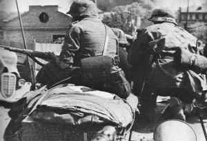 On the back of tanks German troops rushing
